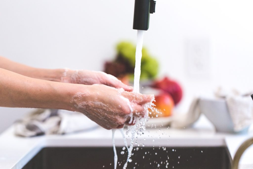 Woman washing her hands in the kitchen sink.